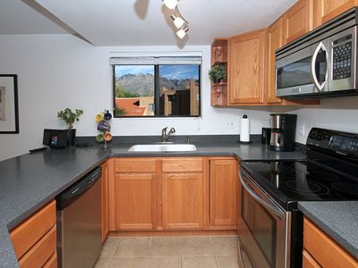 Kitchen with corian countertop; stainless steel appliances; mountain views