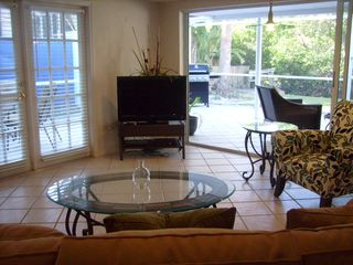 Living room with wall of windows looking out to lanai - Siesta Key house vacation rental photo
