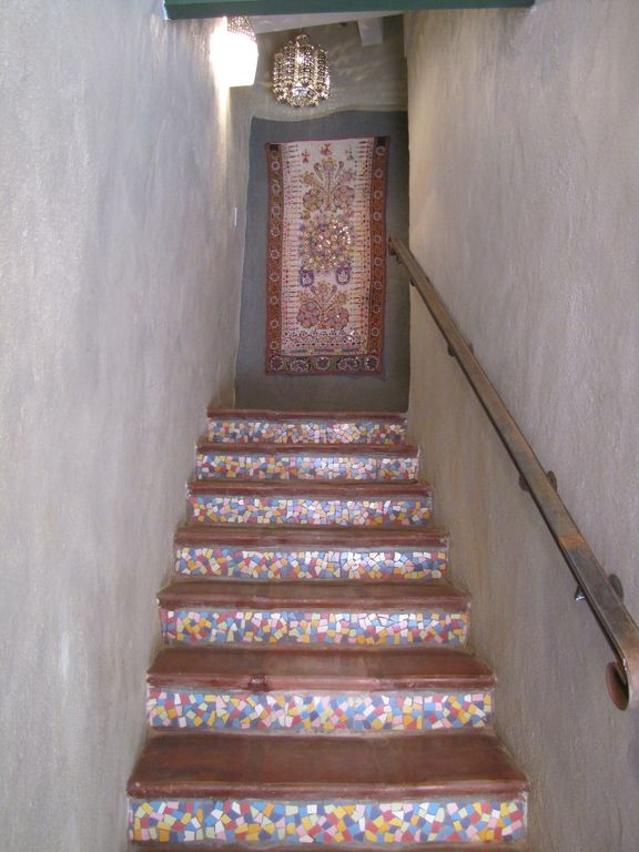 Mosaic tiled stairs to first floor with Indian tapestry