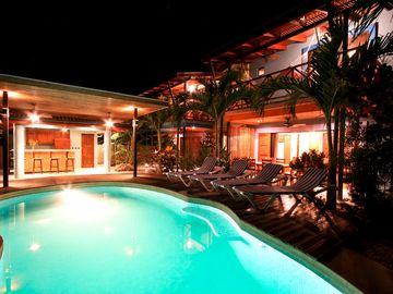 at night by the pool, rancho/bar with full bath, deck chairs