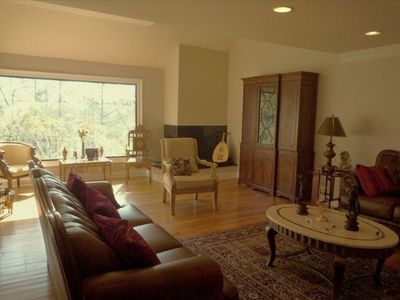 Formal living area w/corner fireplace & large window overlooking woods and pool