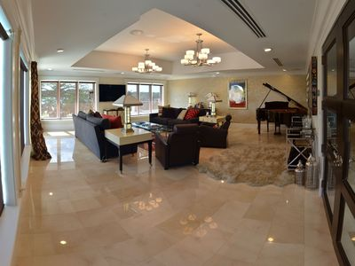 Living room with concert piano and pool and lake views
