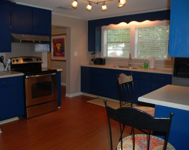 Large, sunny kitchen with new flat top stove and breakfast bar