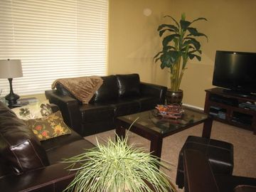 living room with leather furniture and flat screen tv