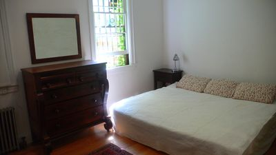 master bedroom with king size bed, heirloom antiques, windows overlooking patio