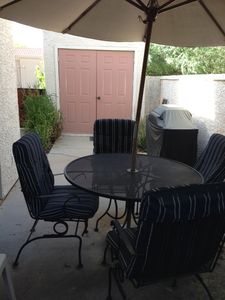 Patio with umbrella, table and grill