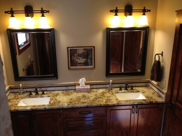 Portion of large bathroom with dual sinks & large decorative tile shower.
