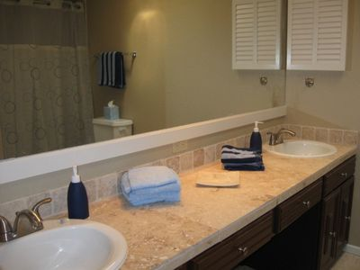 Hall Bath with dual sinks, tub and shower combo. Tile floors.