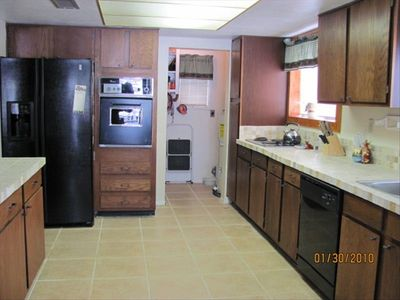Large, fully stocked kitchen with contemporary tile countertops and floor