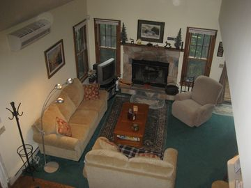 Living room view from upstairs with wood fireplace, A/C and comfortable seating.