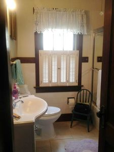 Updated full bath with warm tile floors, full tub with shower, and linen closet.
