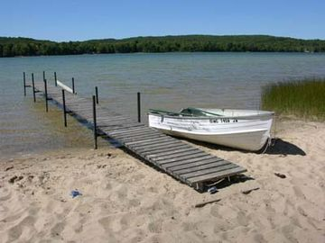 Sandy beach and fishing boat has oars ready to row!