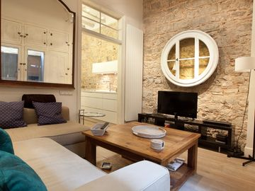 Living room. Exposed stone walls and nice restored vitrine hanged on the wall