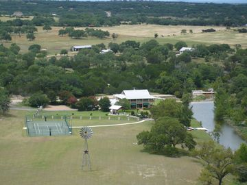 Dripping Springs house rental - View from hilltop of house, pavilion & pool, tennis court, & creek