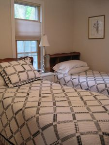 Cottage bedroom -twin beds, dresser, TV, closet and door to bathroom. W/D too!