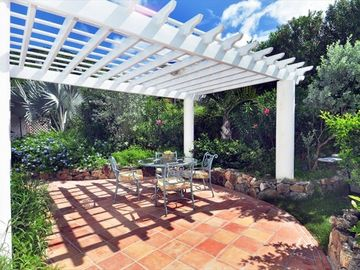 Outdoor dining area among lush tropical gardens and hummingbirds