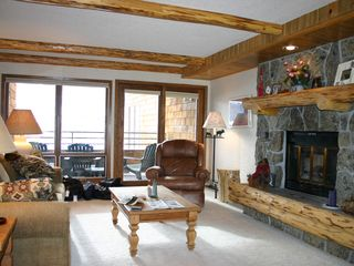 Big Sky condo photo - Living room with fireplace, lodgepole pine beams and deck access
