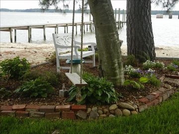 Beachside garden and swing with owner's pier in background.