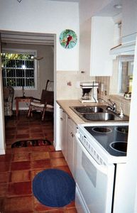 A galley kitchen with tiled floor and counters makes cooking and clean-up easy!