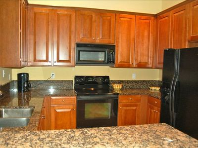 Cook meals in well equipped kitchen with cherry cabinets and granite countertops