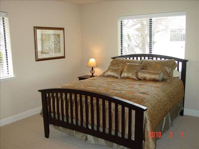 Spacious bedroom with view of Clear Lake and queen size bed.