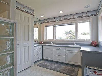 The upstairs bathroom  features double sinks, shower/bath and a  great view.