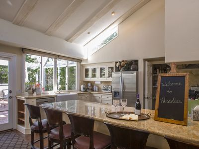 Gourmet kitchen with bar seating for 6 looks out on open floor plan. Hang time!