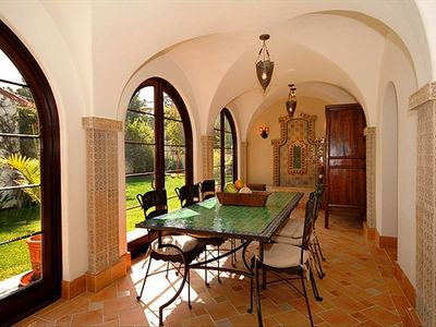 Loggia features moroccan dining table that seats 8 and moroccan tiled fountain.