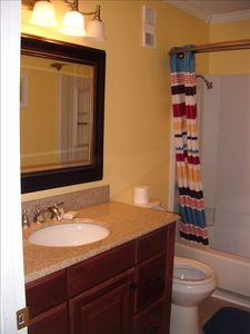 All new hallway bath- new vanity, granite countertop, mirror, toilet, tile floor