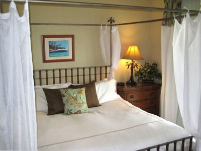 Master bedroom suite with king size Tommy Bahama poster bed and private lanai.