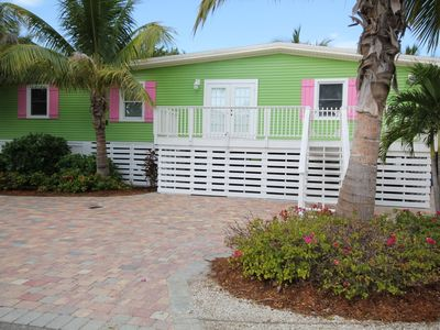 Very Colorful Green Home with Pink and White Trim.