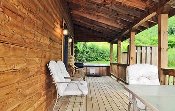 Covered Porch with Deck Furniture; hot tub located at end of porch.