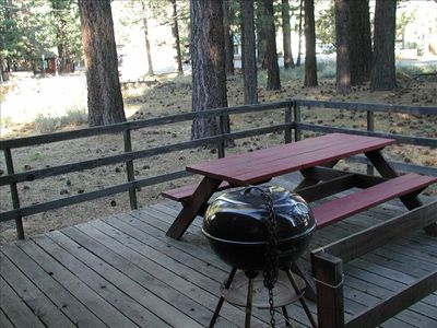 Rear deck with charcoal BBQ. Beautiful view of surrounding trees and yard.