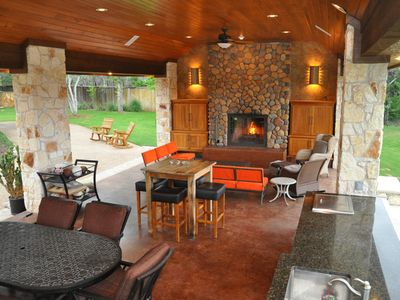 Pavilion with kitchen, three grills, ice maker, fireplace, and flat screen TV.