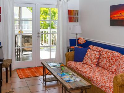 French doors in living room open to tropical sun porch.
