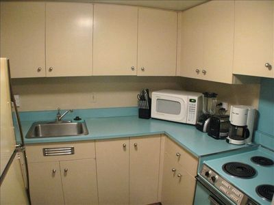 Fully equipped kitchen with stove, microwave and large refrigerator/freezer.