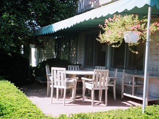 Water Mill house photo - Outdoor front patio with large teak table, awning and view of Mecox Bay