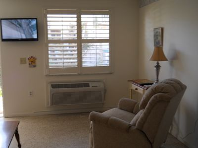The living room offers a comfy recliner and a flat screen TV