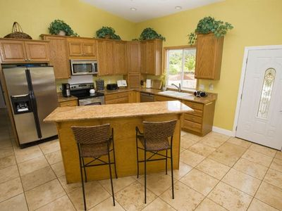 Upstairs Gourmet Kitchen with Stainless Steel Appliances and Breakfast Bar