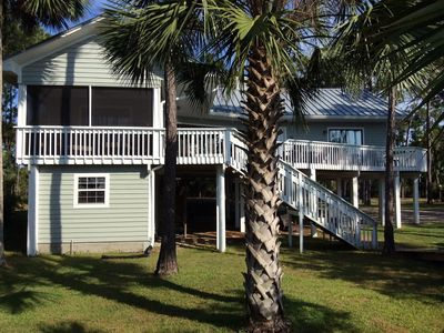 Bayside view of our one-story home with screened porch and wraparound deck.