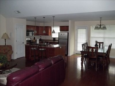 A panoramic view of kitchen, dining room, and family room to the left.