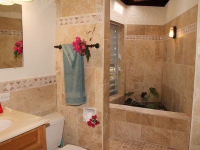 Elegantly tiled en suite bathroom in queen bedroom with walk-in garden shower.