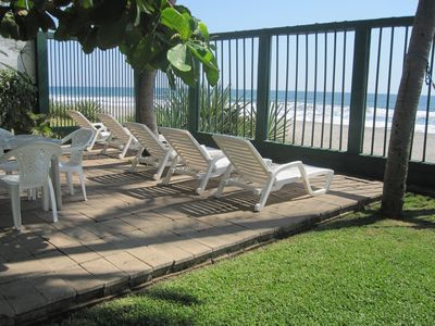 3 lounge chairs with 5 other tables & 4 chairs on each table on this patio area
