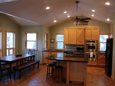 Chef's kitchen with large island, double ovens and adjoining dining room