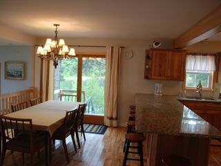 Dining room with views of cove & main shipping channel. Seating for total of 14 - Alexandria Bay cottage vacation rental photo