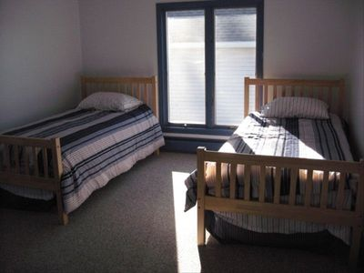 One of four bedrooms with two twin beds, room for a bassinet, crib, or cot too