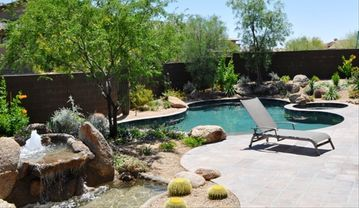 Private back yard with cascading fountain, pool, spa, and outdoor fireplace.