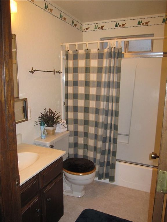 Clean, cabin-themed full bathroom with tub upstairs (1 of 2 bathrooms)