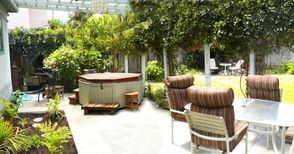 Fully fenced yard, covered patio with hot tub, gas grill, table & comfy chai