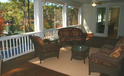 Screened porch over looking lake and pool.